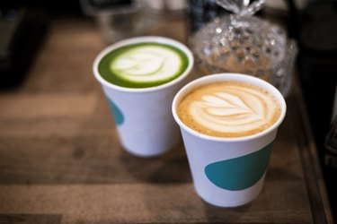 overhead shot of latte and green tea in white to-go cups on wooden counter