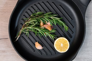 Black frying pan with rosemary, lemon and garlic