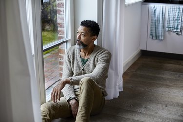 Pensive man sitting on the floor looking out of window