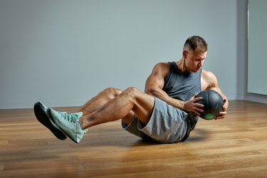 Strong man doing Russian twist exercise with a medicine ball. Photo of man perfect physique on grey background. Strength and motivation