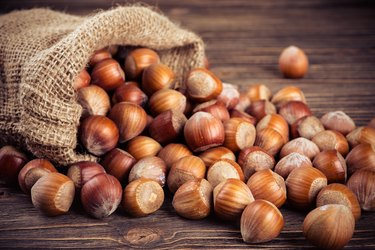 vitamin E-rich hazelnuts in bag on wooden table