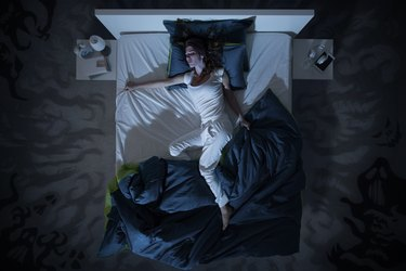 Top view of a woman in bed sweating in her sleep