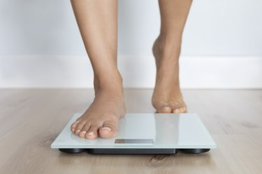 person's feet stepping onto a body fat scale