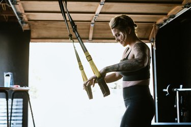 woman exercising with TRX suspension system in garage gym