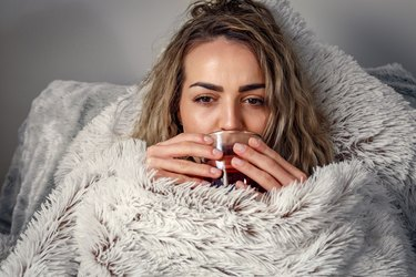 Sick woman in bed, Drinking tea. Vitamins and hot tea for flu. Cold. Woman looking sick and tired