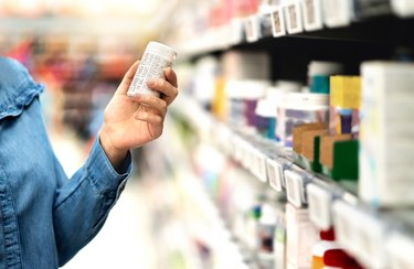 person in pharmacy holding a bottle of vitamin K supplements