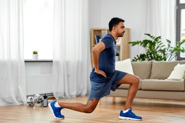 indian man working out and doing a reverse lunge at home