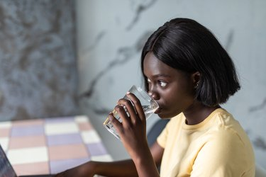 Beautiful young african woman using laptop computer on kitchen while drink water