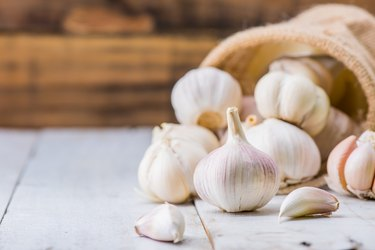 a bunch of garlic bulbs on a wooden table