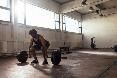 man performing a barbell deadlift exercise in an empty loft with windows