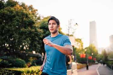 close-up of a man outside in a city park running with relaxed face muscles