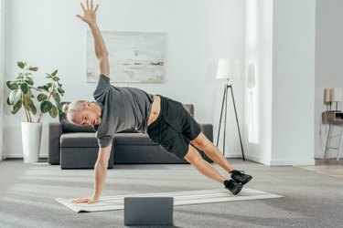 athletic man in sportswear practicing side plank and looking at laptop
