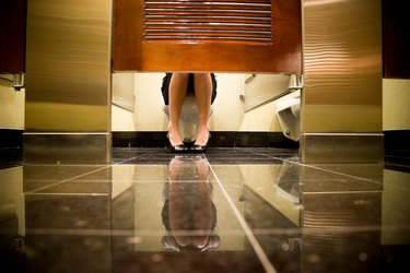 woman sitting on toilet in public restroom