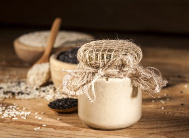 Fresh calcium-rich sesame tahini in a glass jar and seeds in wooden bowls and spoons
