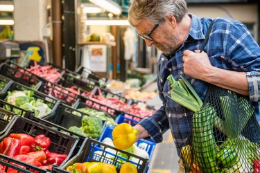 Man grocery shopping for Fruits and Vegetables with mesh reusable bag