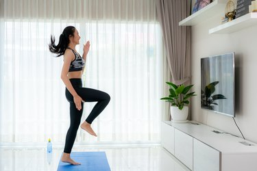 Asian woman doing a low-impact dance cardio workout in her living room