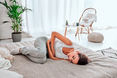 Woman in painful expression holding hands against belly suffering menstrual period pain, lying sad on home bed