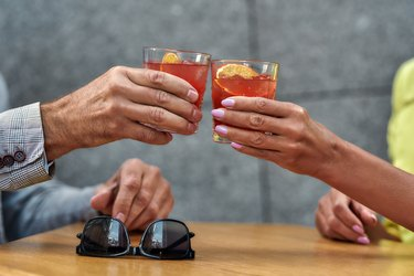 Man and woman's hands holding cocktails while sitting in cafe outdoors