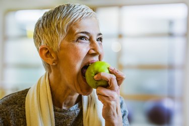 Mature athletic woman eating an apple after exercising in health club.