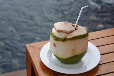 Fresh coconut water drink with white plate, on the corner of lattice table, beside the pool