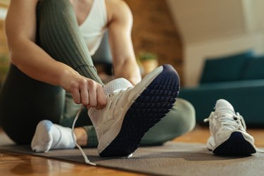 Close-up of athletic woman with athlete's foot putting on sneakers