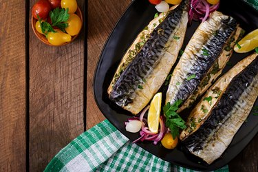 CoQ10-rich baked mackerel with herbs and garnished with lemon on a black plate on a wooden surface.