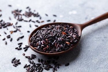 Tyrosine-rich black wild rice in a wooden spoon on a grey stone background