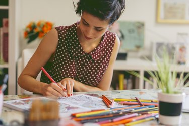 A woman coloring in an adult coloring book at home