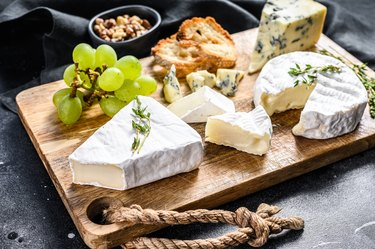 Cheese plate with Camembert, brie and blue cheese with grapes and walnuts. Black background. Top view