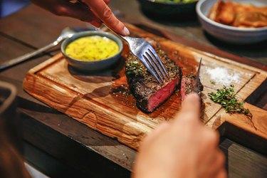 leucine-rich steak on wooden cutting board with sauce