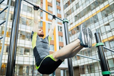 Man doing hanging L-sit, strengthening body on workout ground