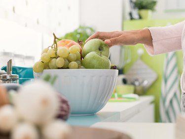 Woman's hand taking an apple from a fruit bowl