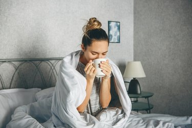 Girl drinks a drink from a mug in bed