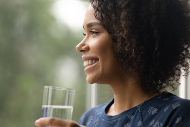 Close up smiling African American woman holding glass of water