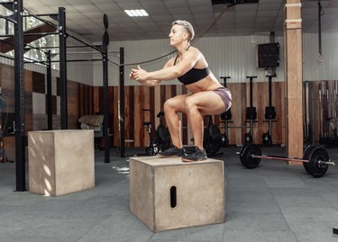 Sporty woman doing box jumps in gym. Sportwoman jumping on wooden box on health gym club.