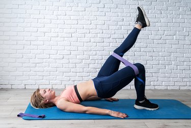 Woman doing exercise for glute hip bridge with a leg up abduction using rubber resistance band