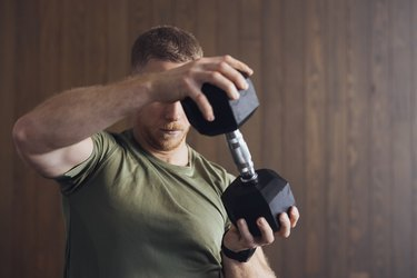 muscular man lifting single dumbbell