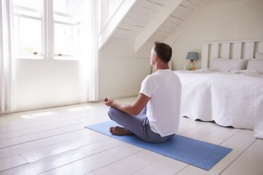 back view of an older man meditating in his bedroom, as a natural remedy for enlarged prostate