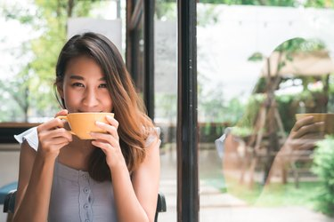young woman drinking warm anti-bloating tea enjoying it while sitting in cafe.