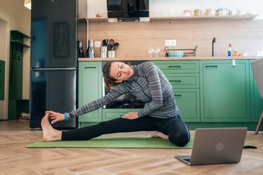 woman working out at home in her kitchen to combat inflammation