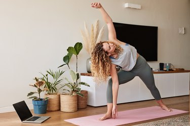 woman with curly hair doing the triangle pose yoga hip opener as part of a yoga flow for tight hips