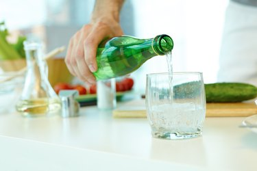 person pouring mineral water from a green bottle