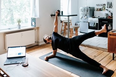 Adult man does a side plank pose during yoga workout at home office