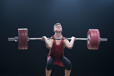 Male weightlifter performing clean and jerk lift