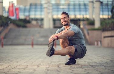 Happy athletic man doing a single-leg squat outside