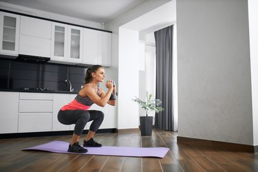 Woman performing sumo squat with dumbbell.