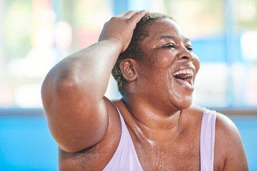 Close-up portrait of a woman at the gym laughing and doing fun exercises