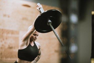 fit woman doing a single-arm landmine press shoulder exercise