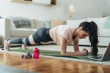 woman holding a plank and doing an ab workout in her living room with her laptop