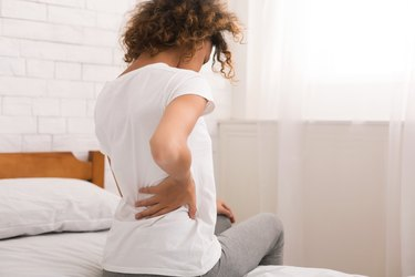 African-american woman having back pain after sleep